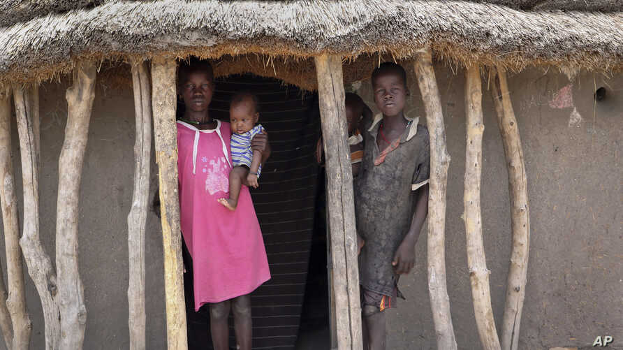 In this photo taken May 2, 2018, children stand in the doorway of their home as they watch their mother prepare food she received from an aerial food drop by the World Food Program in the town of Kandak, South Sudan.
