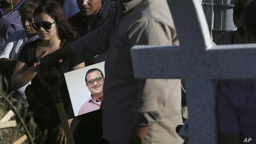FILE - A man carries a portrait of slain journalist Hector Gonzalez Antonio as his daughter, left, mourns during his funeral in Mexico City, Mexico, May 31, 2018.