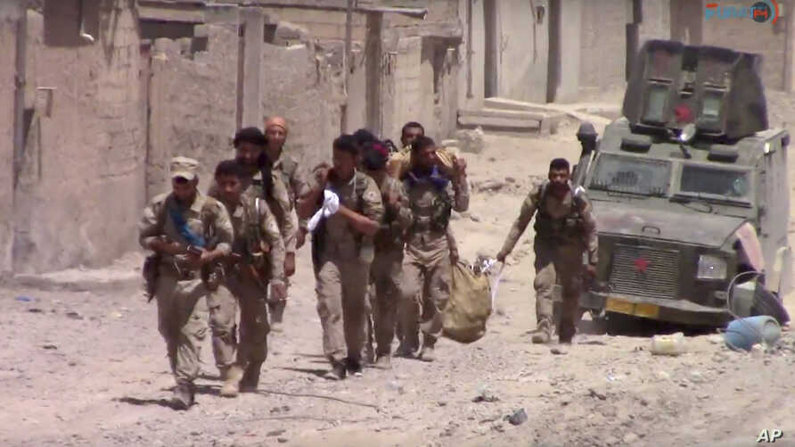 This frame grab from video released July 4, 2017, and provided by Furat FM, a Syrian Kurdish activist-run media group, shows U.S.-backed Syrian Democratic Forces fighters in the eastern side of Raqqa, Syria. The SDF forces have breached the wall arou...
