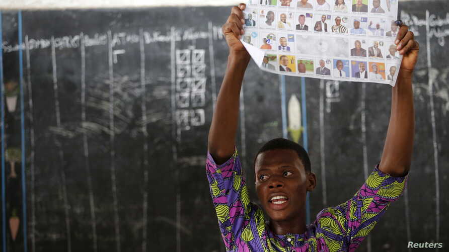 An electoral officer holds up a ballot paper during the count of votes after polling stations closed for the presidential election in Cotonou, Benin, March 6, 2016.