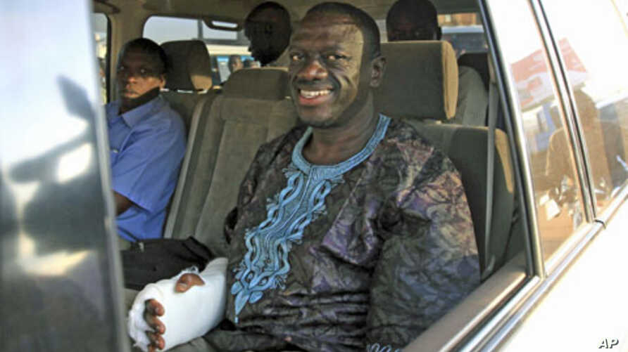 Uganda's Forum for Democratic Change leader Kizza Besigye smiles in a police van after he was arrested and charged for marching in a fourth round of protests against high prices, in the capital Kampala, April 21, 2011