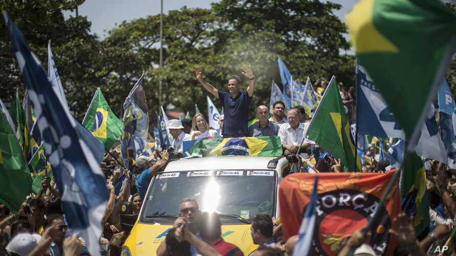Aecio Neves, Brazilian Social Democracy Party presidential candidate, top center, greets supporters while campaigning at Copacabana beach in Rio de Janeiro, Brazil, Oct. 19, 2014.