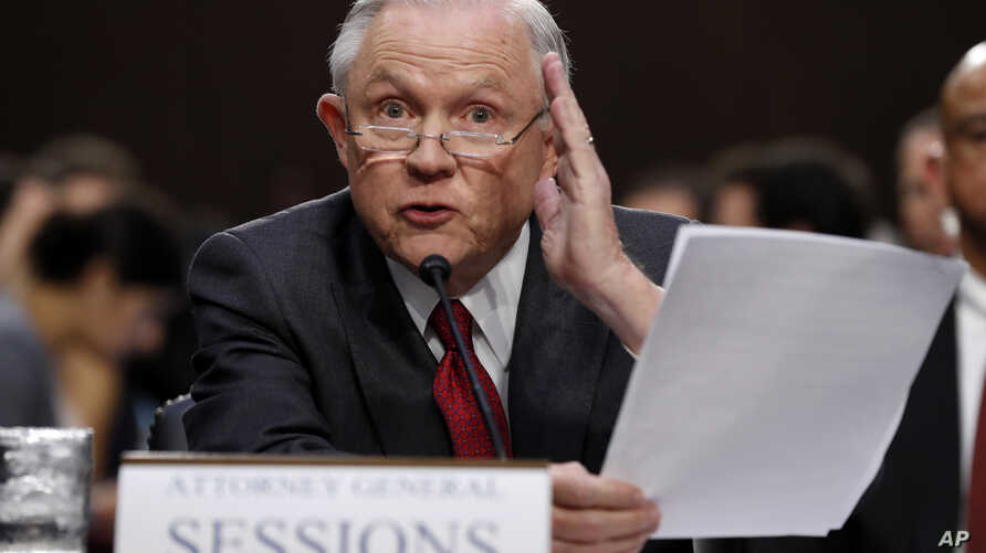 Attorney General Jeff Sessions reads from a statute about his recusal while testifying on Capitol Hill in Washington, June 13, 2017, before a Senate Intelligence Committee hearing.