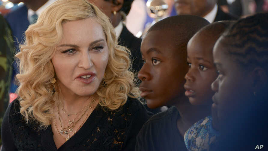 FILE - Madonna, left, sits with her adopted children David, Stella and Mercy, at the opening of The Mercy James Institute for Pediatric Surgery and Intensive Care, located at the Queen Elizabeth Central Hospital in the city of Blantyre, Malawi, July