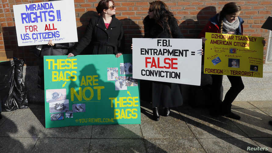 FILE - Demonstrators asserting that evidence in the Boston Marathon bombing was fabricated stand outside the federal courthouse ahead of a pre-trial conference for suspect Dzhokhar Tsarnaev in Boston, Dec. 18, 2014.