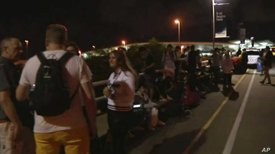 In this image made from a video taken Feb. 2, 2019, travelers stay outside Brisbane International Airport after their evacuation in Brisbane, Australia. A man who falsely claimed to have a bomb and menaced a woman with a knife forced the evacuation o