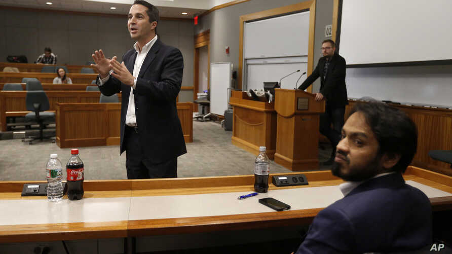 """Lorenzo Vidino, of Milan, Italy, top left, director of the Program on Extremism at George Washington University, addresses an audience during a meeting titled """"Resilience to Violent Extremism: Effective Intervention Approaches,"""" at Suffolk Law School..."""