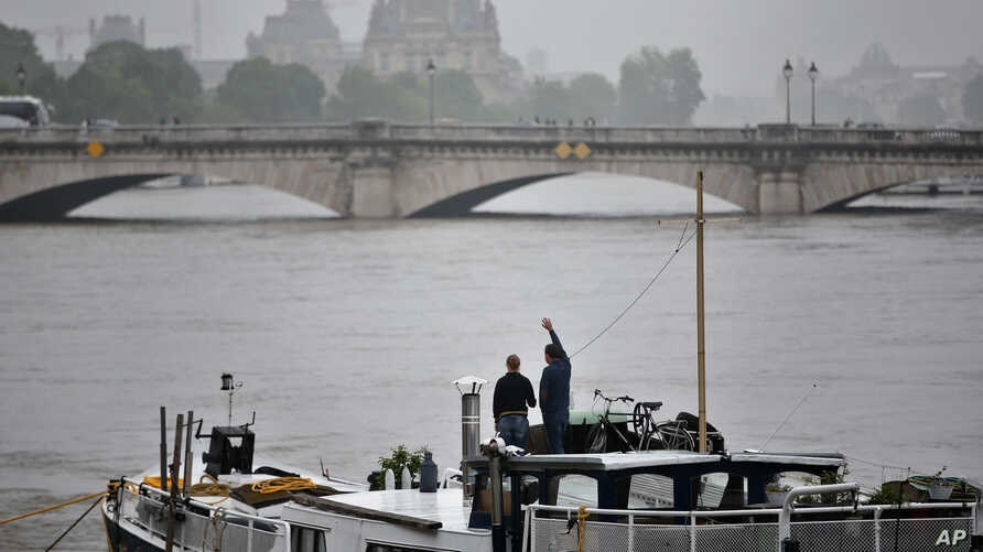 A man waves standing on a barge on the Seine river during floods, in Paris, Sunday, June 5, 2016. Flooding in French capital is part of a weeklong deluge that has swamped large parts of Europe, killing at least 18 people in Germany, France, Romania a