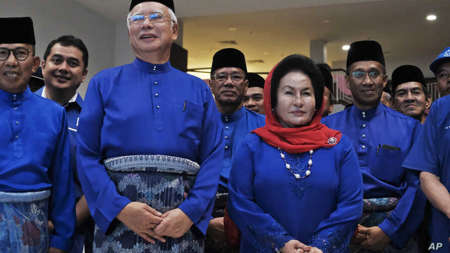 FILE - Former Malaysian Prime Minister Najib Razak, second left in front, and his wife Rosmah Mansor prepare to leave for an election nomination center in Pekan, Pahang state, Malaysia, April 28, 2018.