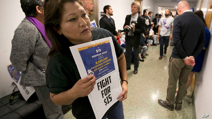 Teamster member Rocio Mejia, a supporter of a proposal to raise the state's minimum wage, joins others outside the Assembly Chambers calling for Assembly members to approve the measure, March 31, 2016, in Sacramento, California.