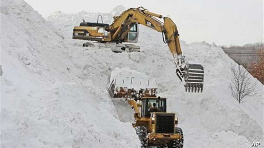 Heavy equipment being used to create a mountain of snow collected from surrounding parking lots at Shoppers World in Framingham, Massachusetts,  January 28, 2011.