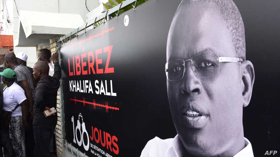 FILE - A banner with a picture of Dakar's mayor Khalifa Sall, in jail awaiting trial for what supporters say are politically motivated embezzlement charges, is on display in front of his offices in Dakar on July 31, 2017, a day after legislative elec