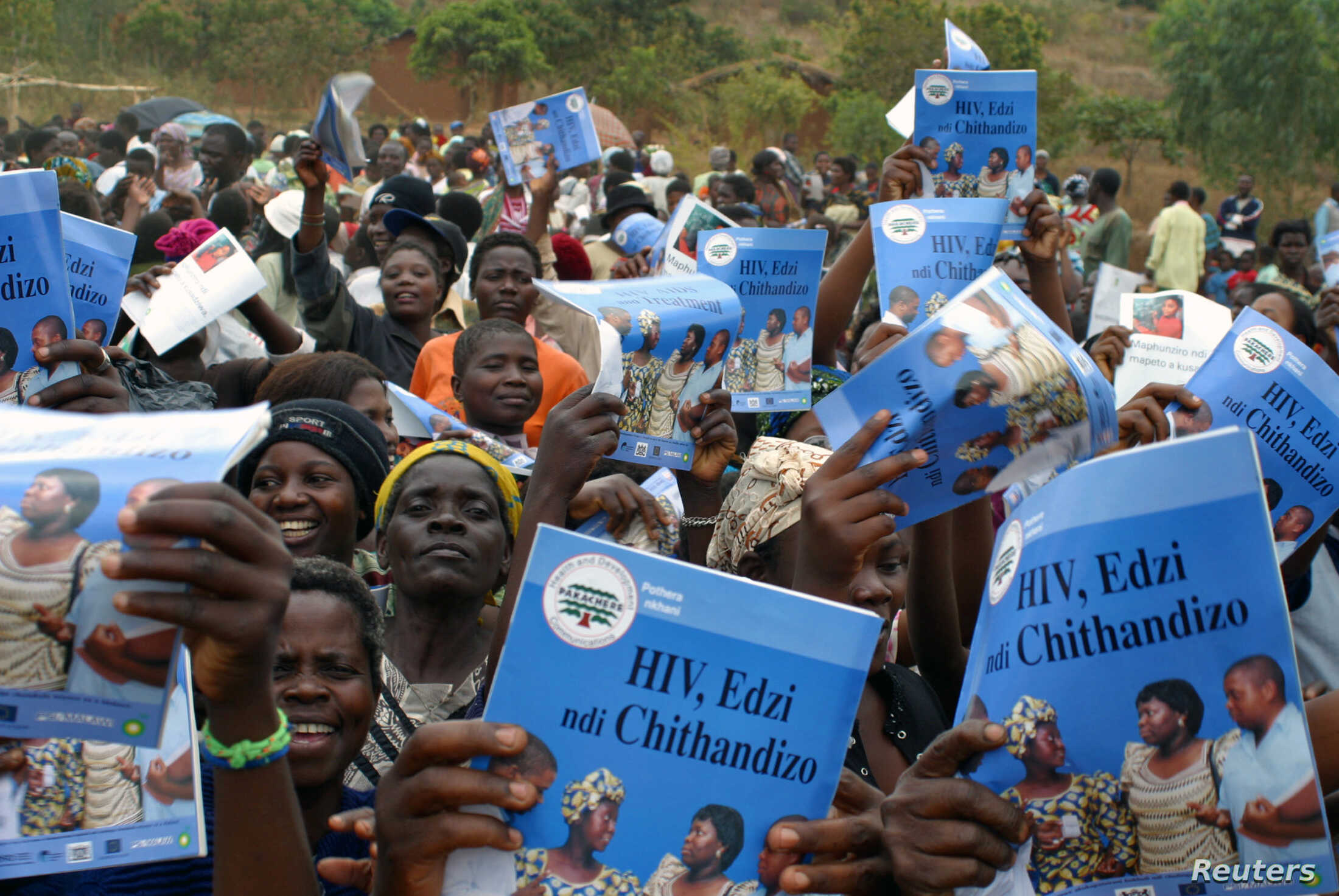 FILE - Parents, guardians, friends and relatives sing traditional songs and carry HIV/AIDS prevention posters during a boys initiation into manhood ceremony in Njoloma village, Malawi.