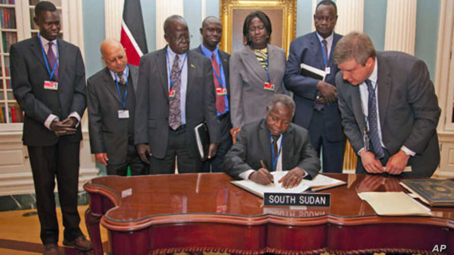 South Sudan's Minister of Finance and Economic Planning Kosti Manibe Ngai (L) signs the treaty to become IMF's newest member as US State Department Treaty Analyst Francis Holleran (R) looks on at the State Department, April 18, 2012 in Washington.