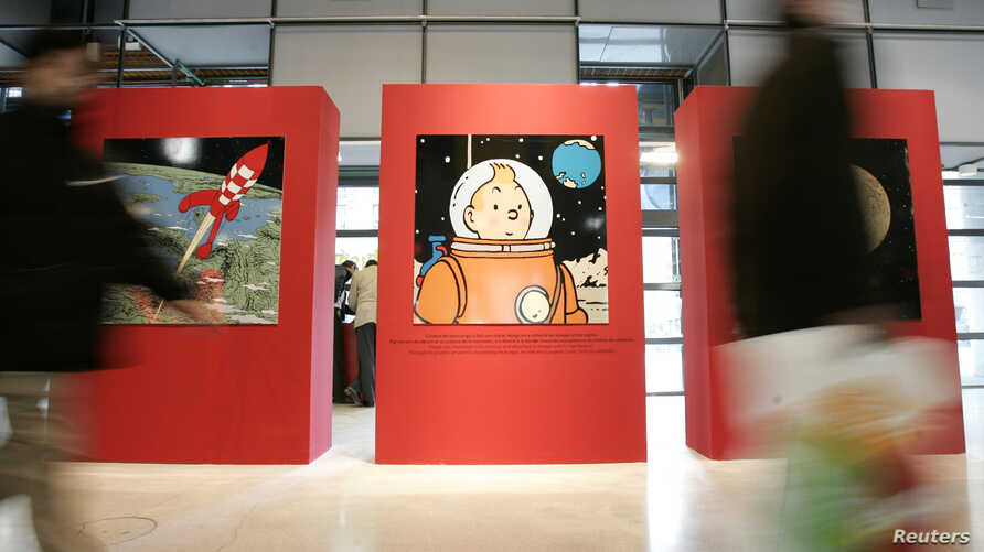 Visitors pass by drawings by Belgium illustrator Herge during a Tintin exhibition in Paris, Dec.19, 2006.  The country enters the space race, as illustrated by the comic-strip hero in the 1950s, with plans to form a Belgium space agency next year.