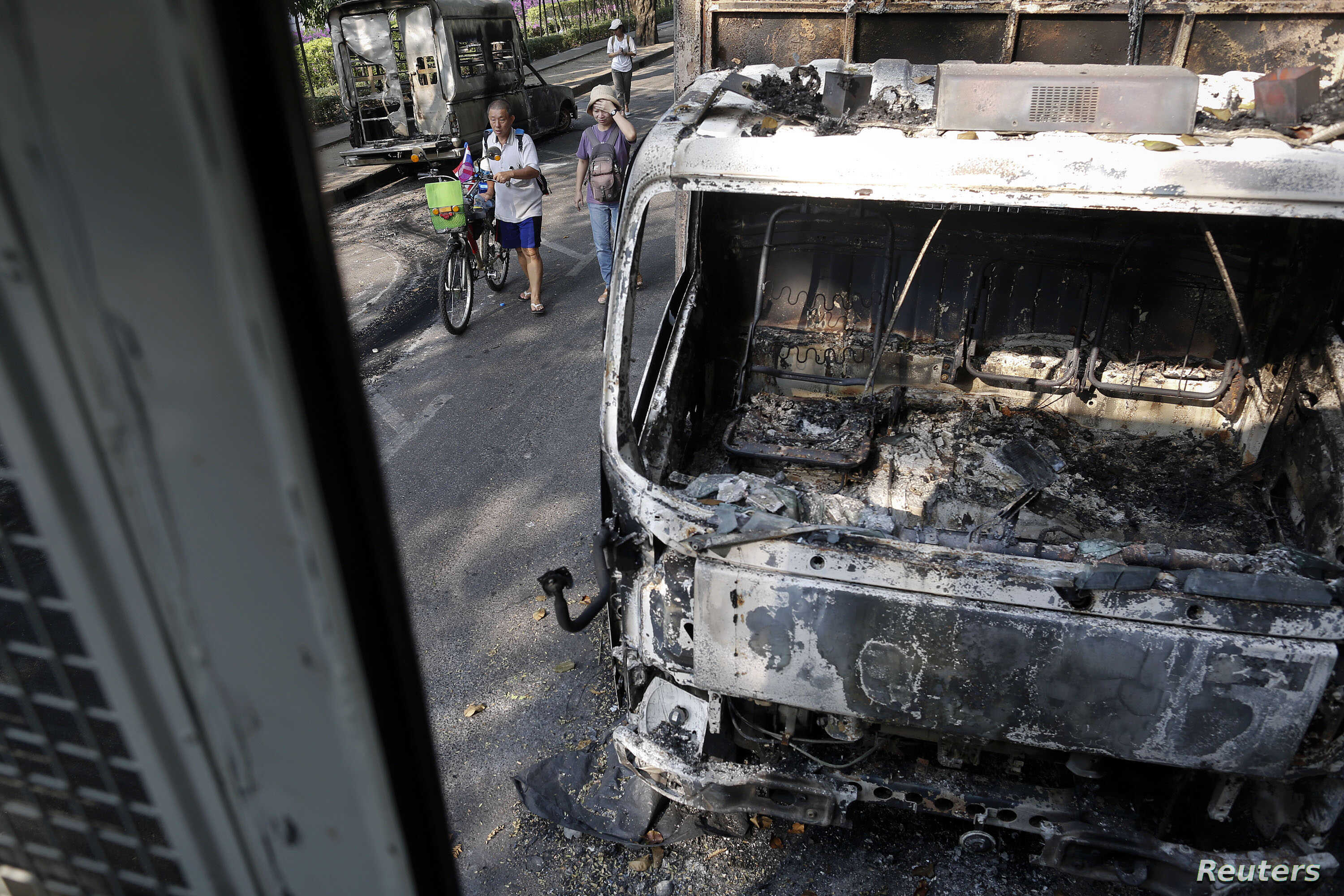 People walk between burnt-out vehicles at the site of recent clashes between anti-government protesters and police near the Government house in Bangkok, Thailand, Dec. 7, 2013.