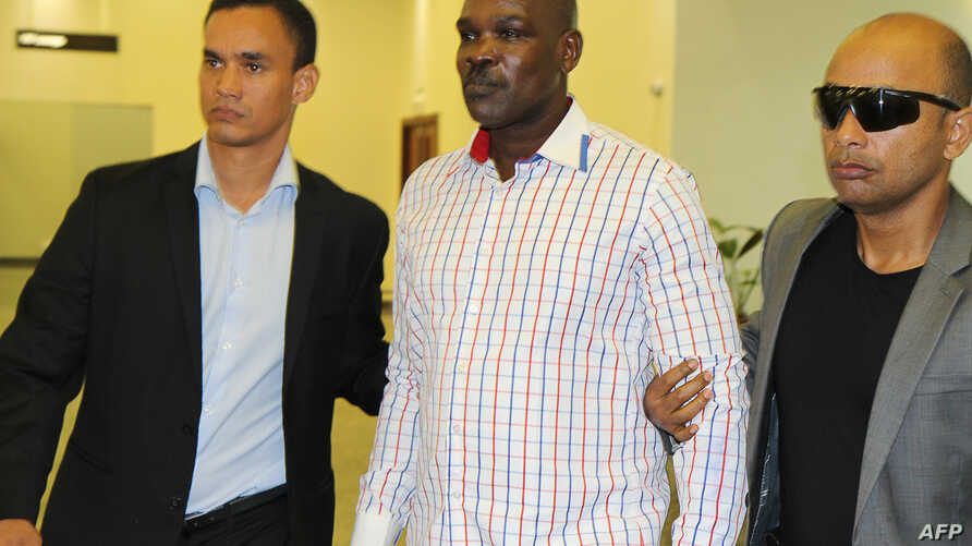 Top level Rwandan genocide suspect Ladislas Ntaganzwa (C) is escorted by security upon his arrival at the airport of Kigali, March 20, 2016.