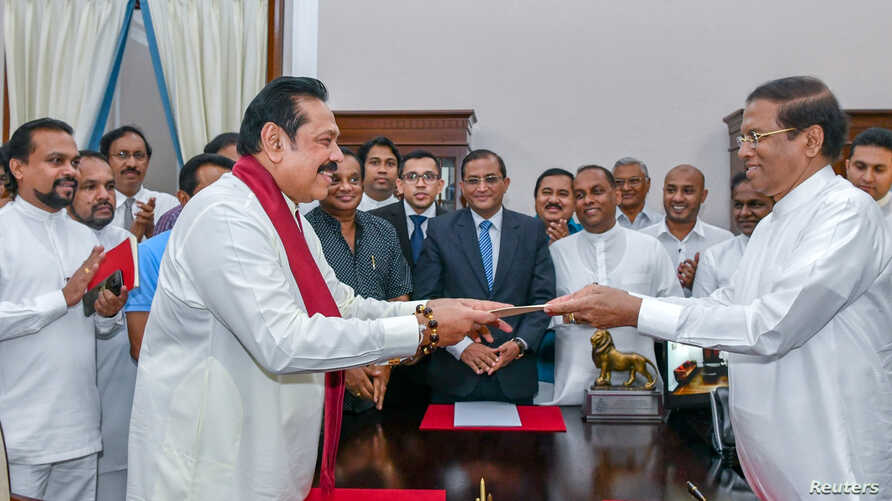 Sri Lanka's former President Mahinda Rajapaksa, front left, is sworn in as prime minister before President Maithripala Sirisena in Colombo, Sri Lanka, Oct. 26, 2018.