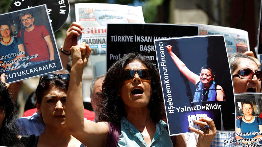 Demonstrators shout slogans as they hold pictures of Ahmet Nesin, Sebnem Korur Fincanci and Erol Onderoglu during a protest against arrest of the three prominent campaigners for press freedom, in front of the pro-Kurdish Ozgur Gundem newspaper in cen
