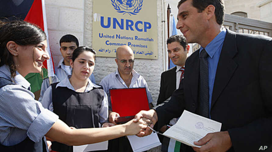 A Palestinian school girl, left, hands a letter, addressed to the United Nations Secretary-General Ban Ki-moon, to UN officer Pascale Soto, right, during a rally to support the Palestinian statehood bid in the United Nations, in the West Bank city of