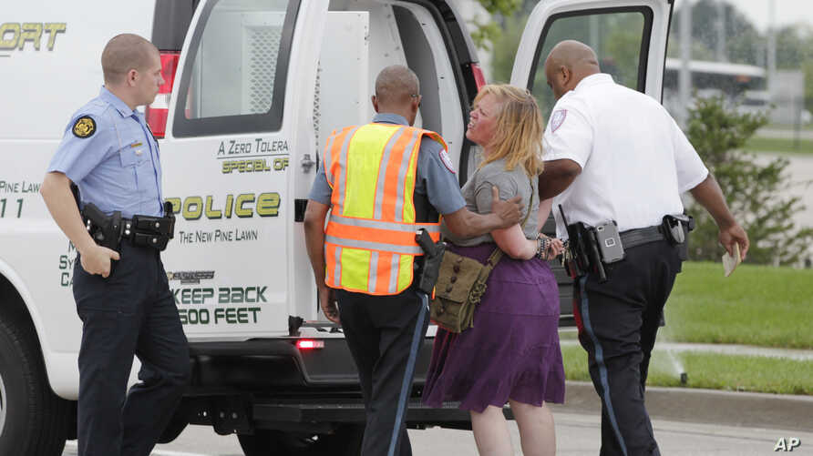 Police arrest a protester after she refused to leave the area during an attempt to shut down Interstate 70 near the St. Louis suburb of Ferguson, Missouri, where Michael Brown, an unarmed, black 18-year old was shot and killed by a white police offic