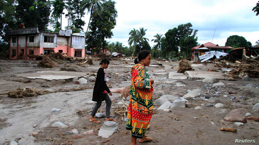 Residents are seen near a mosque in a village devastated by flash floods in Salvador, Lanao del Norte in southern Philippines, Dec. 24, 2017.