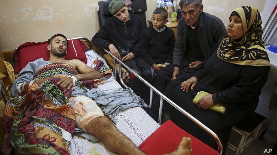Palestinian surfer Raed Jadallah, left, lies on a bed as his father, mother and brothers, visit him at the Shifa hospital in Gaza, April 9, 2018. Jadallah is among the nearly 1,300 people that Palestinian health officials said have been shot and woun