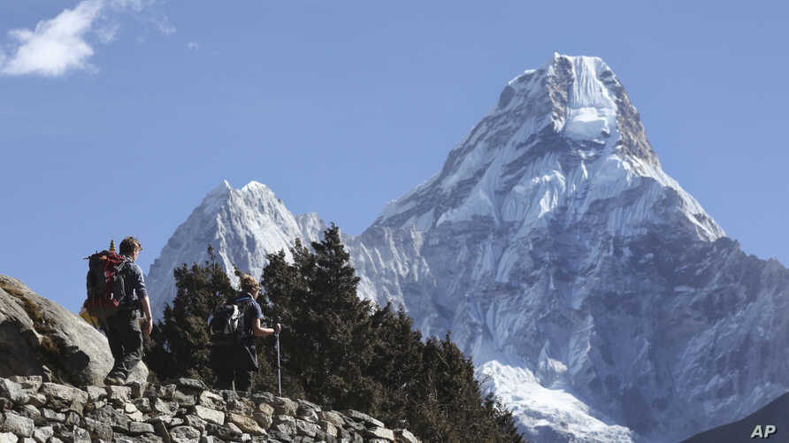FILE - Trekkers make their way to Dingboche, a popular Mount Everest base camp, in Pangboche, Nepal, Feb. 19, 2016. Officials say three foreign climbers; two British Kenton Cool, Robert Richard Lucas, and Mexican David Liano Gonzalez along with three