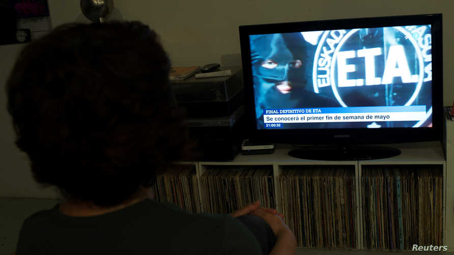 A woman watches a news program announcing the dissolution of armed Basque separatists ETA set for the first week of May, in Guernica, April 18, 2018.