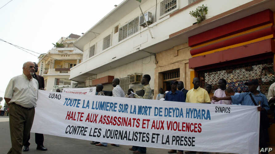 """A group of fifty people hold a banner reading """"Shed light on the death of Deyda Hydara. Stop assassinations and violence against journalists and the press,"""" during a protest in front of Gambia's high commission, 22 December 2004 in Dakar."""