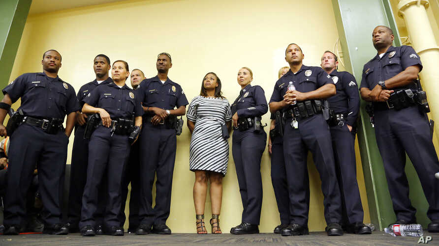 Rodney King's daughter Lora King, 32, stands shoulder-to-shoulder with a group of Los Angeles Police Officers as they meet with a group of young people who have had their own run-ins with police at a meeting of the Los Angeles Conservation Corps, whi