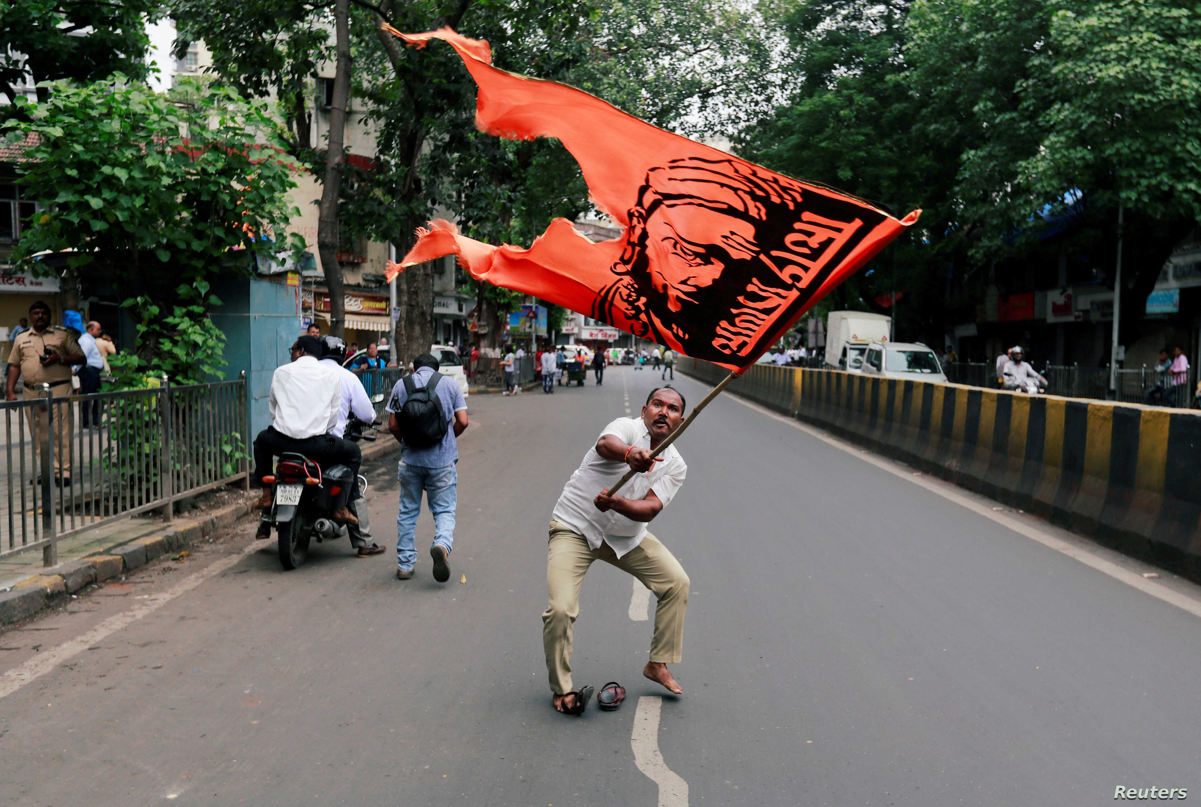 FILE - A man waves a flag as he blocks a road during a protest, organized by Maharashtra state's Maratha community, to press their demands for reserved quotas in government jobs and college places for students in Mumbai, India, July 25, 2018.