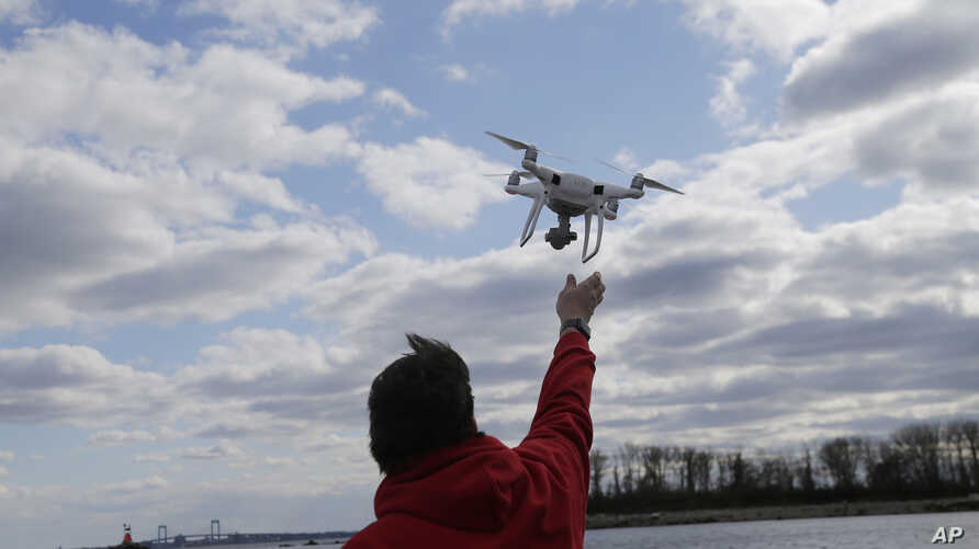 FILE- A drone operator helps to retrieve a drone after photographing over Hart Island in New York, April 29, 2018.