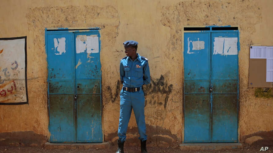 A member of the Sudanese security forces stands guard outside a polling station, on the second day of Sudan's presidential and legislative elections, in Izba, an impoverished neighborhood on the outskirts of Khartoum, Sudan, April 14, 2015.