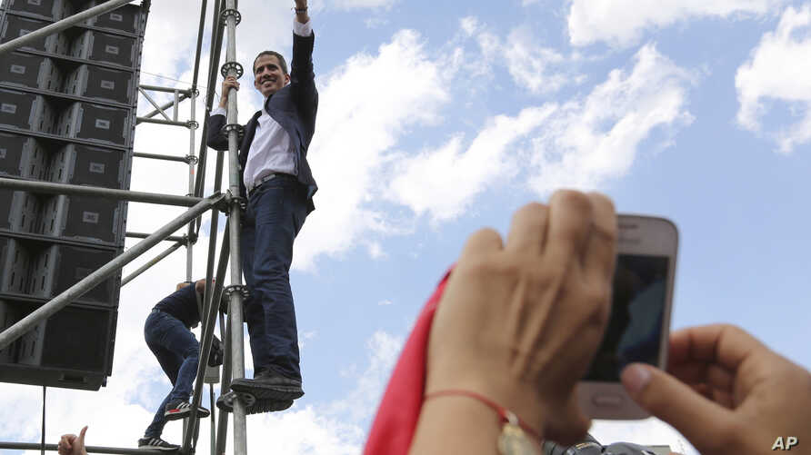 Venezuelan Congress President Juan Guaido, an opposition leader who declared himself interim president, waves from the scaffolding after speaking at a rally demanding the resignation of President Nicolas Maduro in Caracas, March 4, 2019.