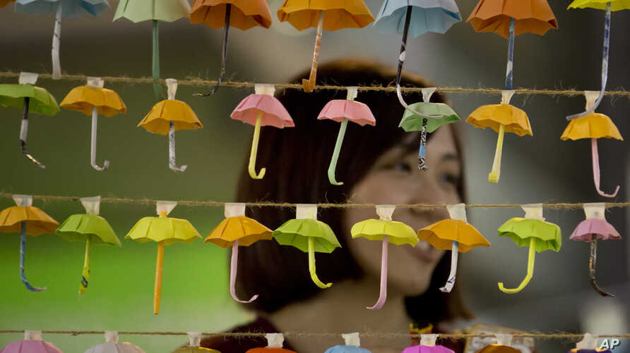 A woman poses for a photo with the paper fold umbrellas at the occupied area in Causeway Bay, a shopping district of Hong Kong, Oct. 21, 2014.