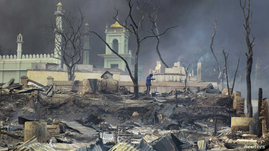 A man stands in front of a mosque as it burns in Meikhtila March 21, 2013. The central Myanmar town declared a curfew for a second night on Thursday after clashes killed 10 people, including a Buddhist monk, and injured at least 20, authorities said.