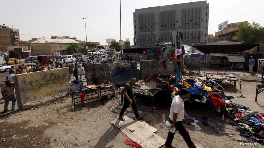 Men walk past the site of a suicide bomb attack in Baghdad, Iraq, September 17, 2015.