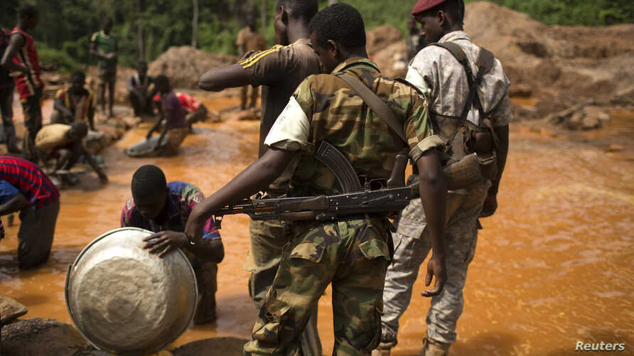 FILE - Former Seleka soldiers look at prospectors as they pan for gold near the open pit at the Ndassima gold mine in the Central African Republic, May 9, 2014.