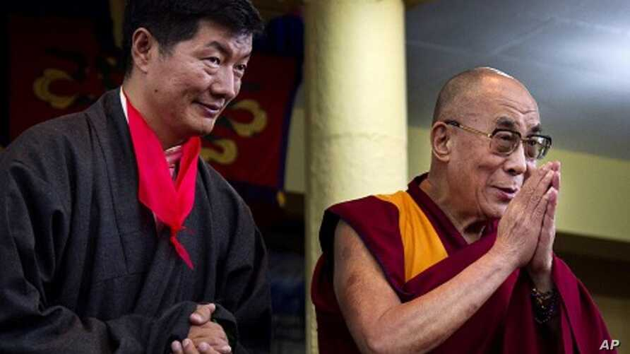 Lobsang Sangay, left, the new prime minister of Tibet's government in exile, stands next to Tibetan spiritual leader the Dalai Lama as he greets the crowd at his swearing-in ceremony at the Tsuglakhang Temple in Dharmsala, India, August 8, 2011