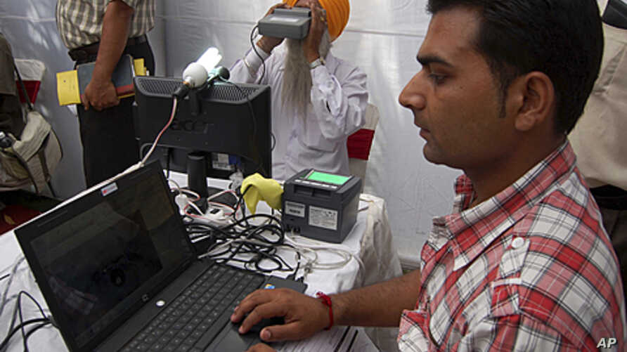 An Indian Sikh (C) looks through an optical biometric reader, which scans and individual's iris patterns, during registration for Aadhaar cards or Unique Identification (UID) cards in Amritsar, (File May 24, 2011).