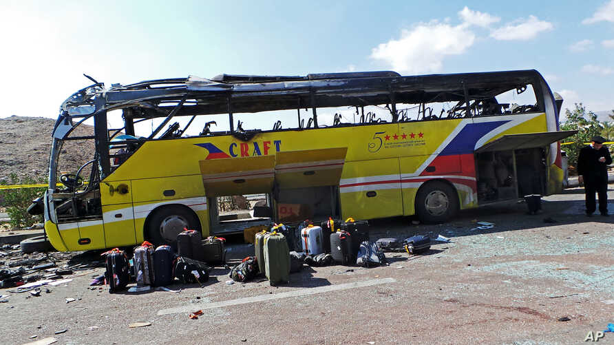 An Egyptian policeman stands guard in front of a damaged bus after a deadly explosion Sunday near the Egyptian border crossing with Israel in Taba, Egypt, Feb. 17, 2014.