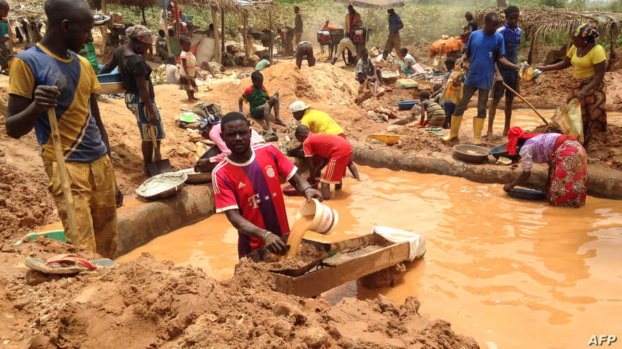 FILE - Miners work at a mining site in the Cameroonian town of Betare Oya, April 4, 2018.