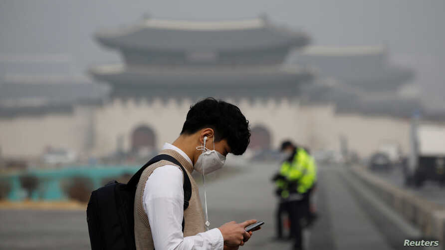 A student wearing a mask uses his mobile phone during a polluted day in Seoul, South Korea, March 5, 2019.