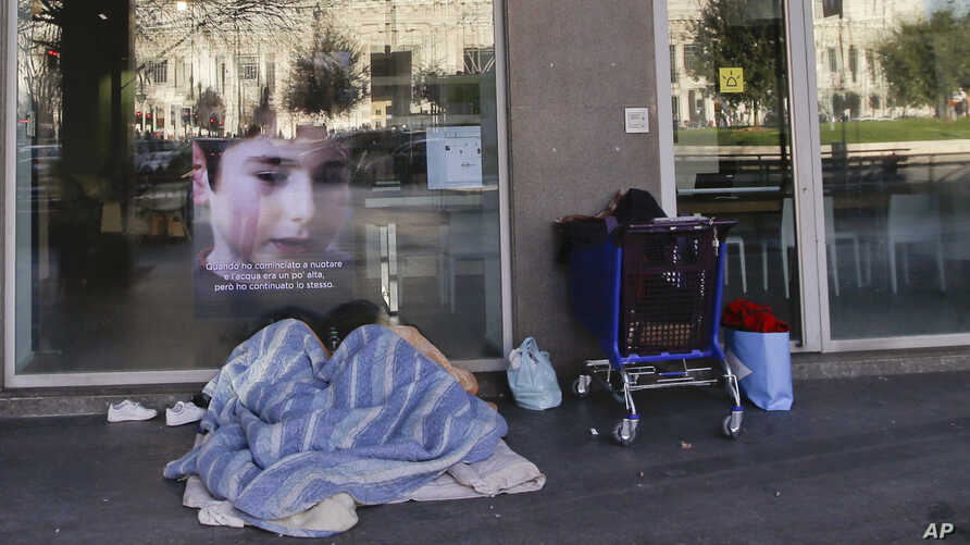 A homeless person sleeps under blankets in front of the entrance of a bank, in Milan, Italy, Jan. 7, 2017. In Italy, subfreezing temperatures were blamed on the deaths of a half-dozen homeless people, while heavy snows and high winds resulted in re-r