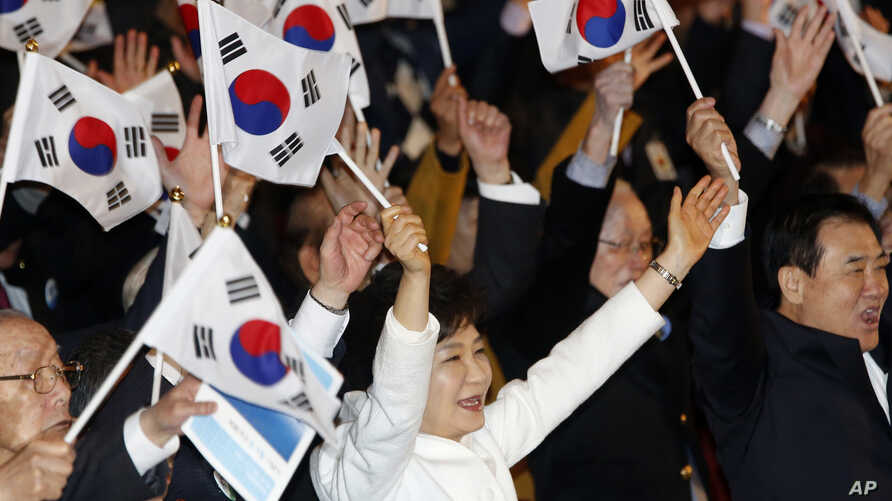 South Korean President Park Geun-hye, center, cheers with her national flag during a ceremony to celebrate the Independence Movement Day, the anniversary of the 1919 uprising against Japanese colonial rule, in Seoul, March 1, 2014.