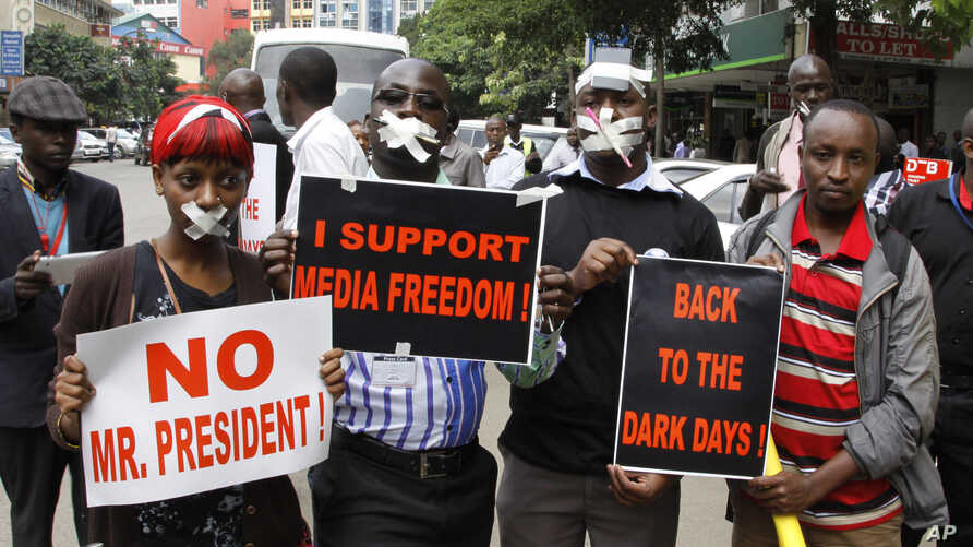 FILE - Kenyan journalists wear tape over their mouths to signify being silenced, Dec. 3, 2013.