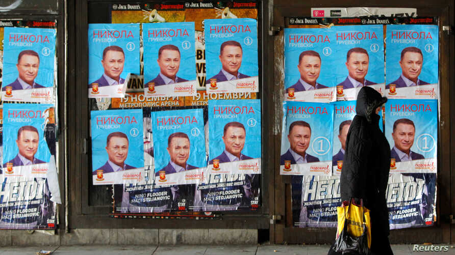 People walk next to posters of the candidates for the early parliamentary elections in Skopje, Macedonia, Dec. 8, 2016.