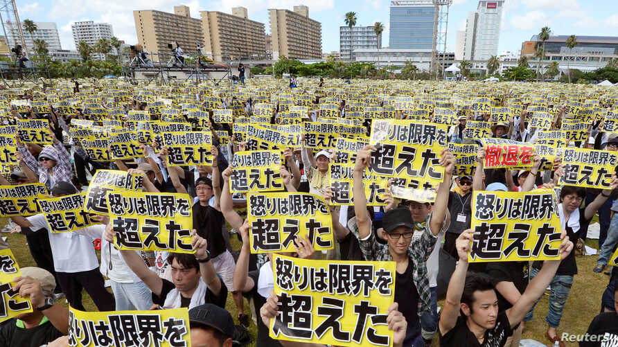 """Protesters raise placards reading """"Anger was over the limit"""" during a rally against the U.S. military presence on the island and a series of crimes and other incidents involving U.S. soldiers and base workers, at a park in the prefectural capital Nah"""