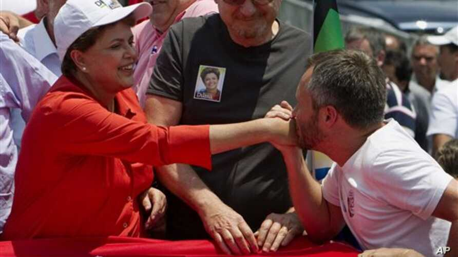 A supporter kisses the hand of Dilma Rousseff, presidential candidate of the ruling Workers Party, as Belo Horizonte mayor Marcio Lacerda looks on, during a campaign rally in Belo Horizonte, Brazil, 30 Oct 2010